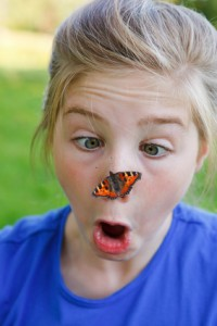 girl surprised of a butterfly on her nose